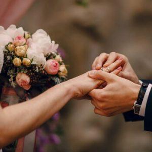 Groom putting ring bride's finger